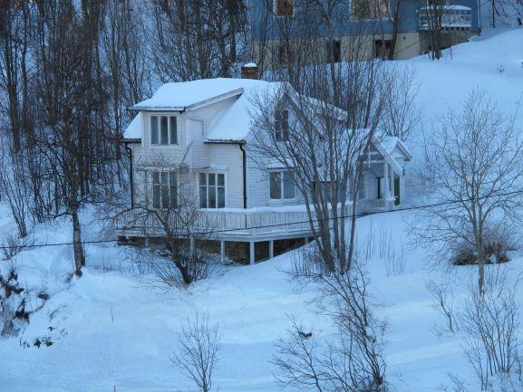 Ein verschneites Haus an der Küste