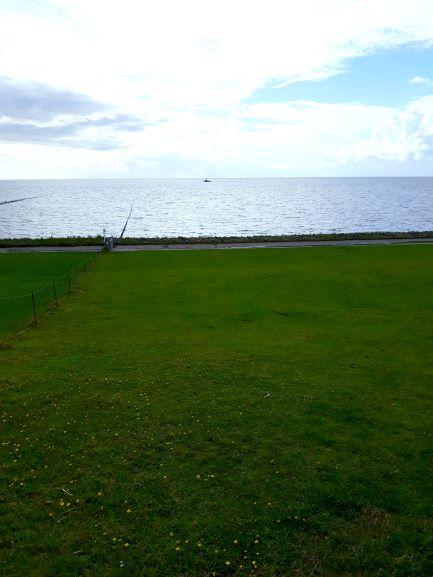 Urlaub im Ferienhaus an der Nordseee: Blick vom Deich auf die Nordsee bei Flut